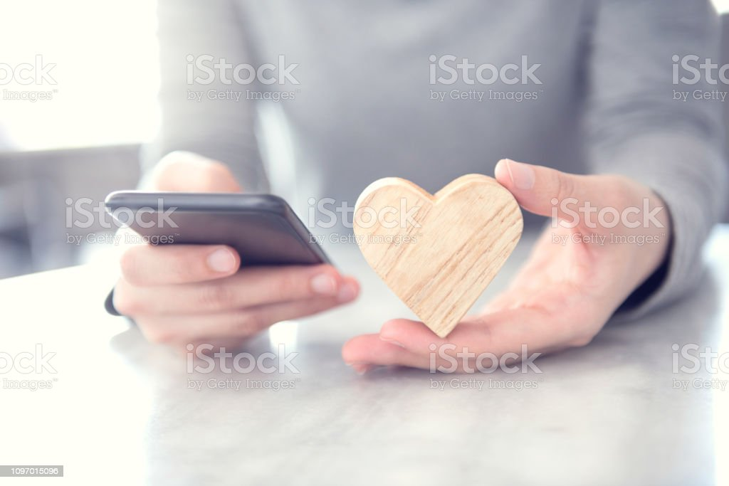 Woman sending love text message on mobile phone with symbol wood...