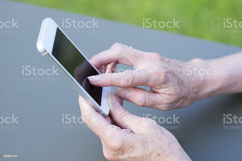 Woman Senior using a mobile phone in garden royalty-free stock photo