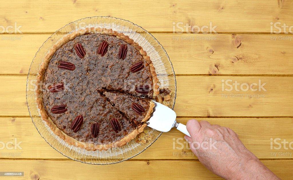 Woman serves a slice of pecan pie stock photo