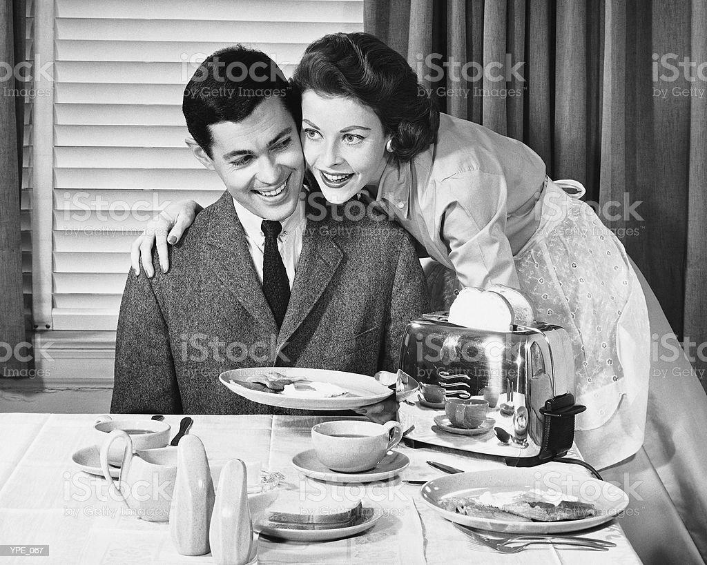 Mujer sirve un hombre de desayuno foto de stock libre de derechos