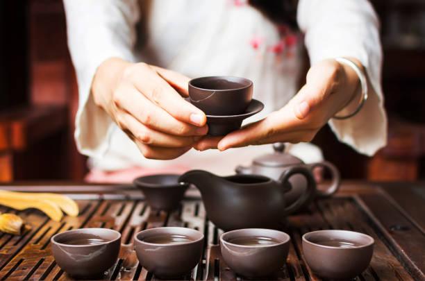 frau serviert chinesische tee in eine tee-zeremonie - keramikteekannen stock-fotos und bilder