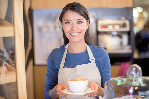 Woman serving coffee at a cafe stock photo