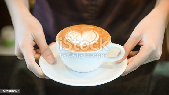 istock woman serving coffee while standing in coffee shop. Focus on Latte art hearth shape cup in female hands while placing of coffee on counter 856956474
