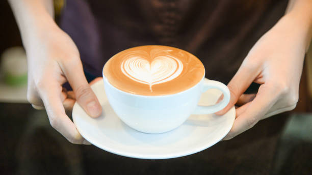 woman serving coffee while standing in coffee shop. focus on latte art hearth shape cup in female hands while placing of coffee on counter - barista making coffee stock photos and pictures