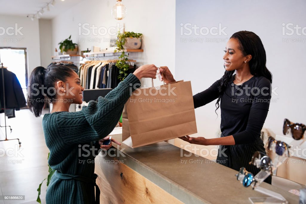 Woman serving customer at the counter in a clothing store stock photo