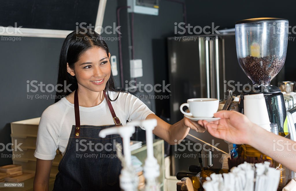 Woman serving customer in coffee shop stock photo