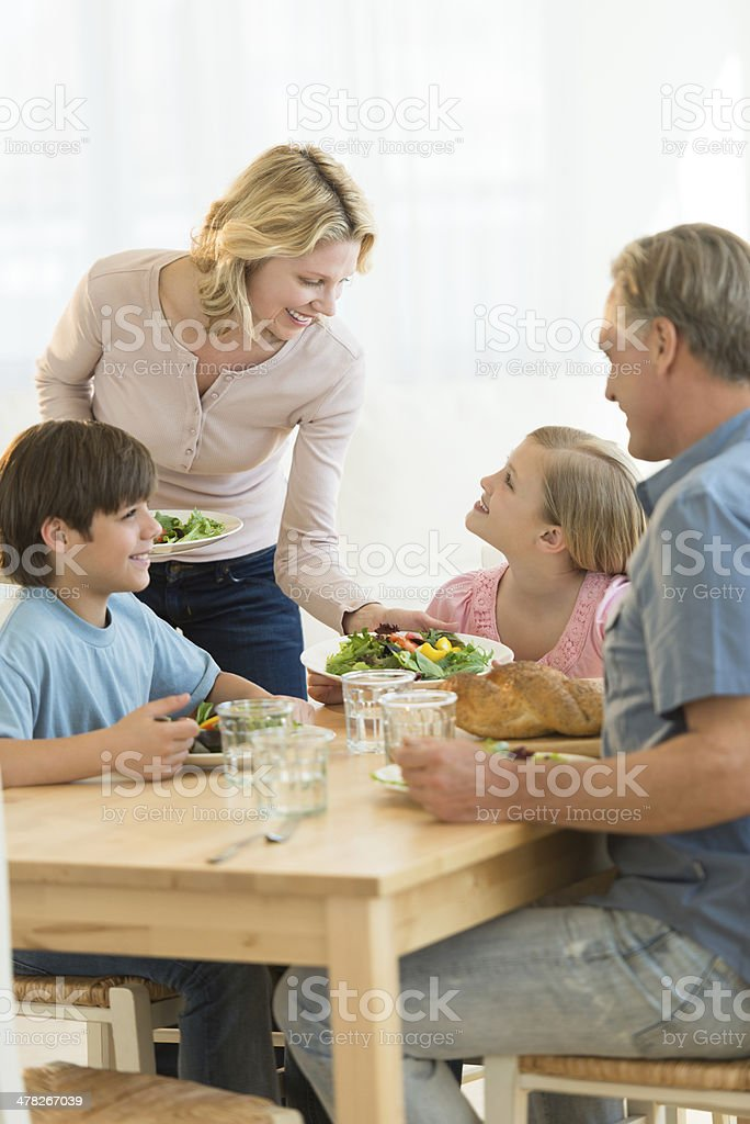 Woman Serving Food To Daughter At Dining Table royalty-free stock photo