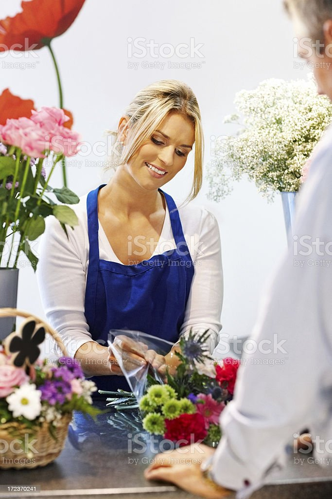 Woman serving male customer in florist and smiling royalty-free stock photo