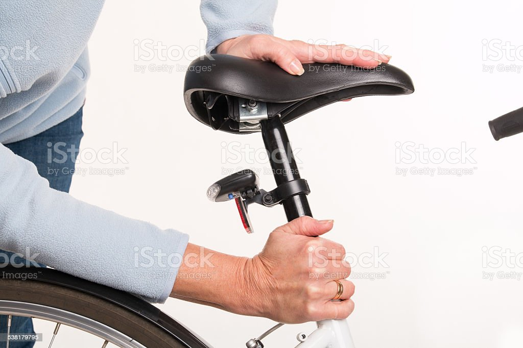 Woman sets height of  bicycle saddle before cycling stock photo