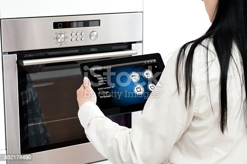 istock Woman sets up oven baking programme. 532174490