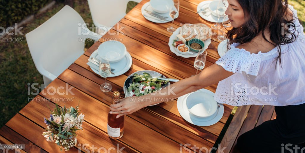 Woman setting a dining table for housewarming stock photo