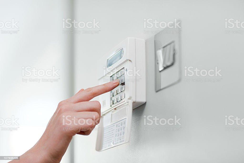 Woman setting burglar alarm stock photo