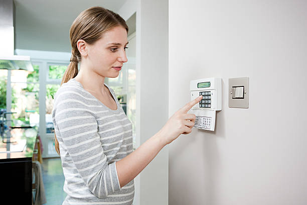 woman setting burglar alarm - alarm stock pictures, royalty-free photos & images