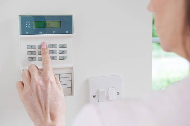 Frau die Fernbedienung auf Home Security System – Foto