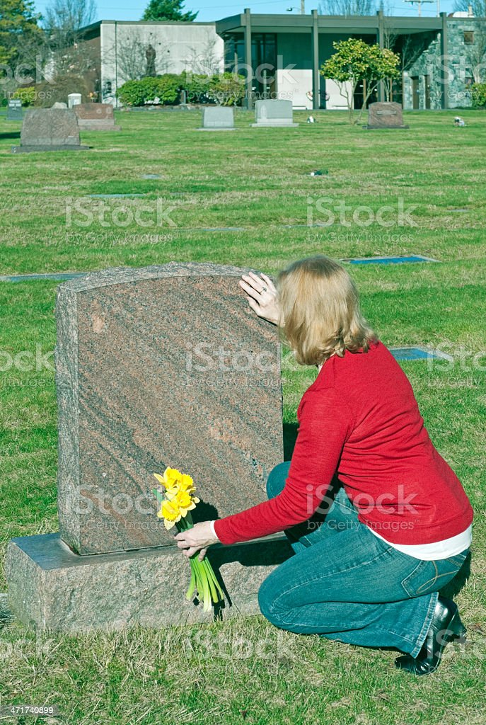 Woman setting daffodils at grave site in cemetery royalty-free stock photo