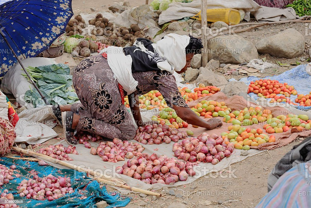 Woman setting her stall on the floor. Sunday market-Senbete-Ethiopia. 0040 stock photo