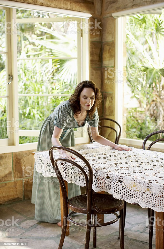 Woman setting tablecloth on table royalty-free stock photo