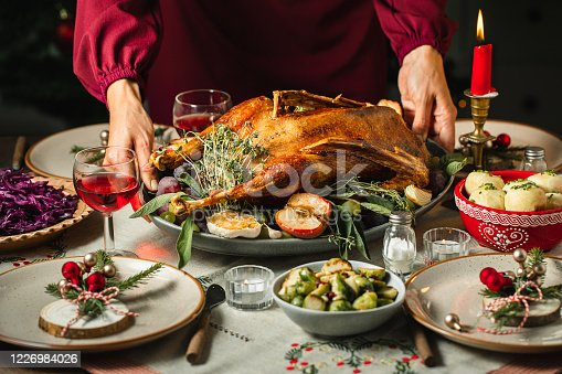 Close-up of woman's hands setting the table, serving roast duck for Christmas dinner.