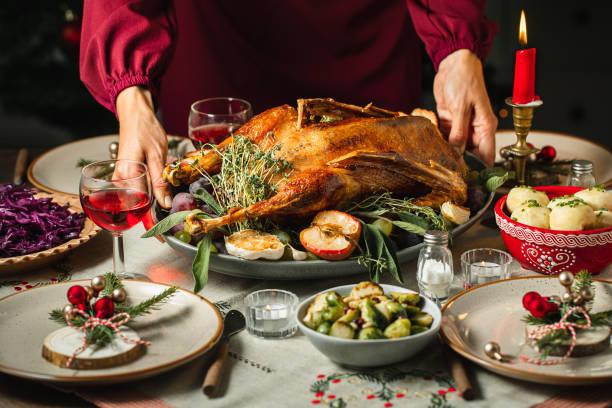 vrouw die de lijst voor het diner van kerstmis plaatst - kruisbloemenfamilie stockfoto's en -beelden