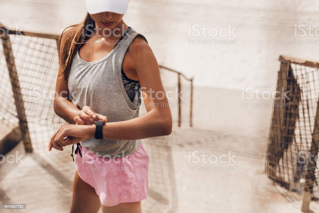 Woman setting their fitness app before workout stock photo