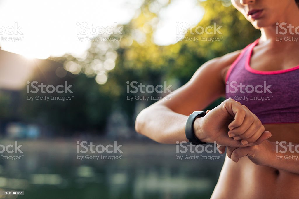 Woman setting up the smartwatch for running stock photo