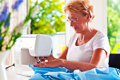 Cheerful senior woman sewing on sewing machine at home.