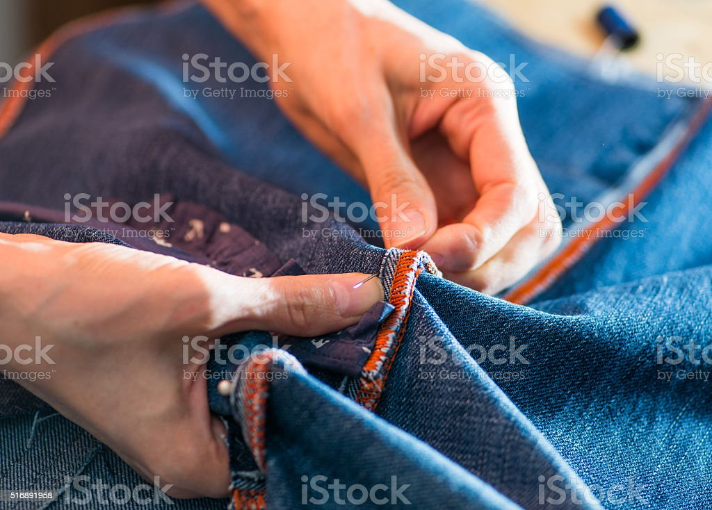 woman sewing denim stock photo