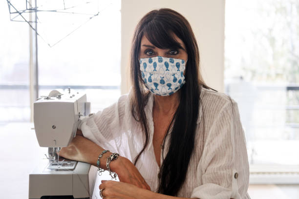 Woman sewing homemade protective mask stock photo