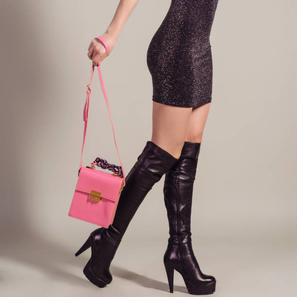frau sexy beine in stiefel mit handtasche. einkaufs- und - neontasche stock-fotos und bilder