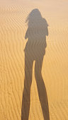 Young woman shadow on the sand of the beach, top view