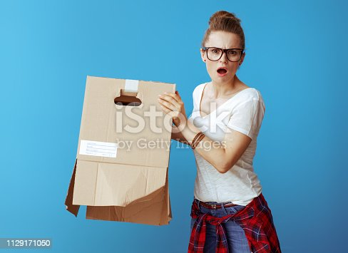 istock woman shakes out something from old cardboard box on blue 1129171050