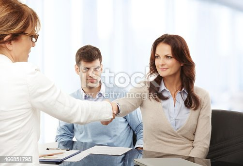 istock Woman shaking hands with couple discussing documents 466851795