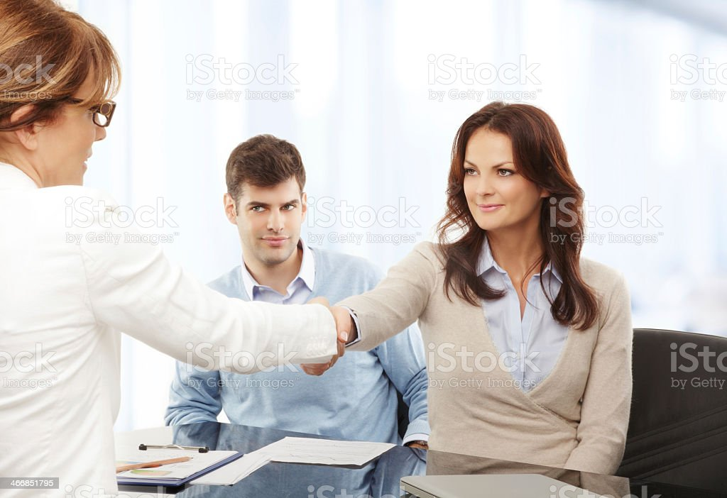 Woman shaking hands with couple discussing documents stock photo