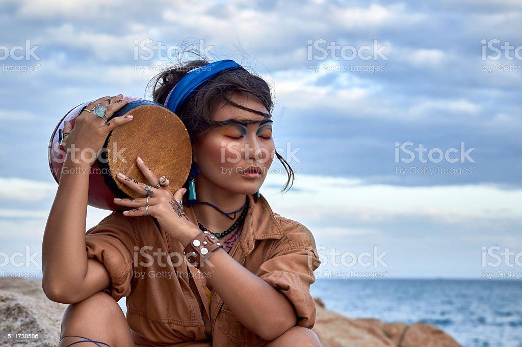 Woman shaman with drum, in mountain sea. Ethnic fashion photoshoot. stock photo