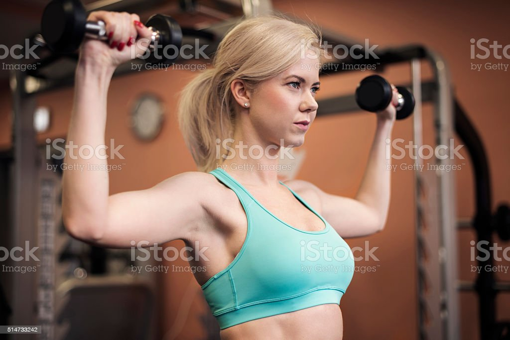 Woman shaping her shoulders at the gym stock photo
