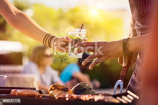 Closeup of young woman hand passing a drink to a man while preparing barbeque. Girl sharing glass with fresh lime juice during outdoor bbq. Hand of man taking mojito while preparing beef on bbq.