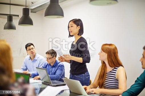 Group of business people sitting at table with a female colleague standing at reading a document. Female professional sharing the finance report with staff in meeting.