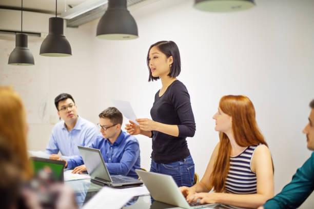 Frau teilt Finanzbericht mit Team in Sitzung – Foto
