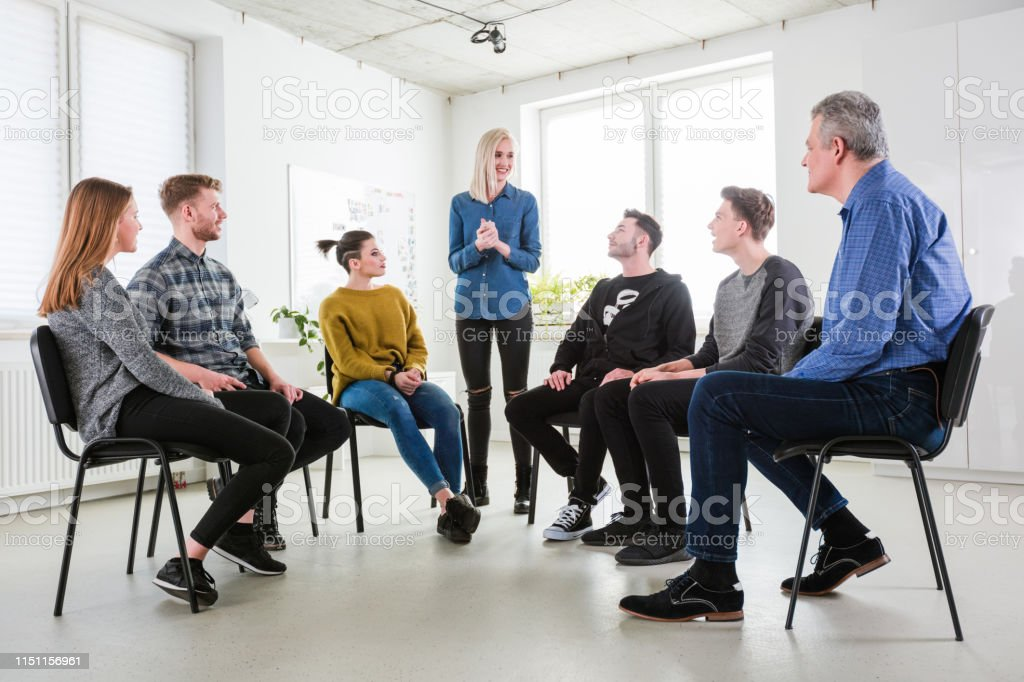 Woman sharing her views to friends and therapist Smiling young woman sharing her views to friends and social worker. Mental health therapist is having community outreach session with students. They are in university lecture hall. 18-19 Years Stock Photo