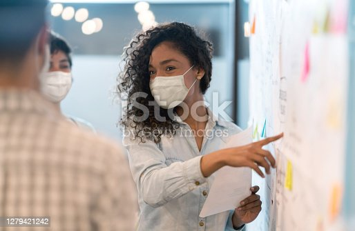 Woman sharing ideas with her team at a creative office while wearing facemasks during the COVID-19 pandemic