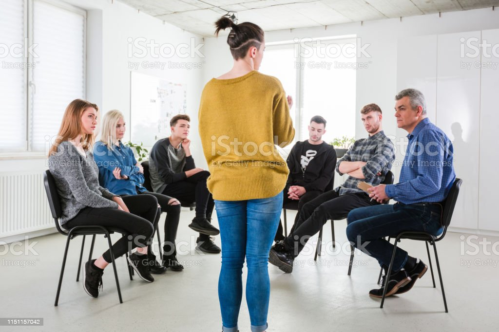 Woman sharing views to friends and social worker Young woman sharing her views to friends and social worker. Mental health therapist is having community outreach session with students. They are in university lecture hall. 18-19 Years Stock Photo