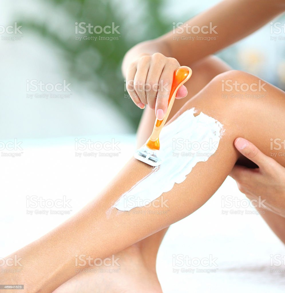 Woman shaving her legs. stock photo