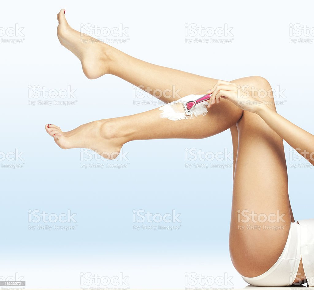 Woman Shaving Legs stock photo