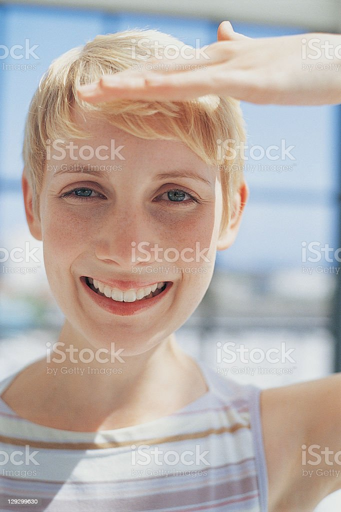 Woman shielding eyes from sun stock photo