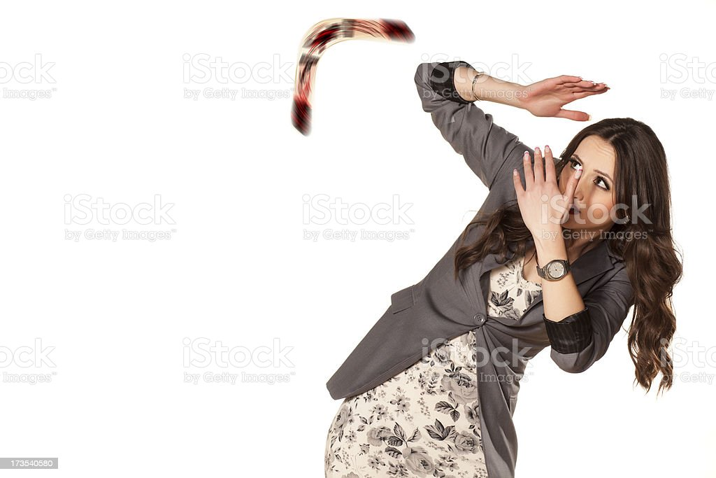 Woman shielding herself from flying boomerang stock photo