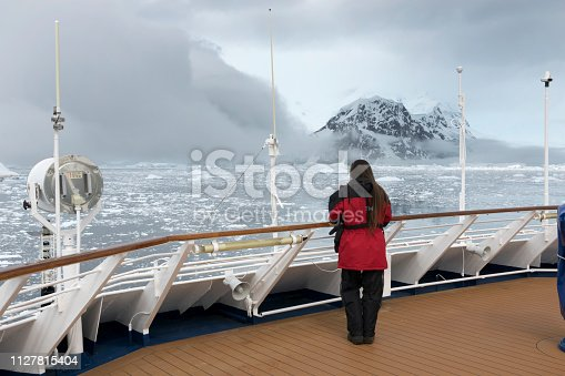Looking from the ship's observation deck, a woman with long hair enjoys the spectacular mountain glacier views of Neko Harbor in the ice filled Andvord Bay on the Antarctic Peninsula, Antarctica.