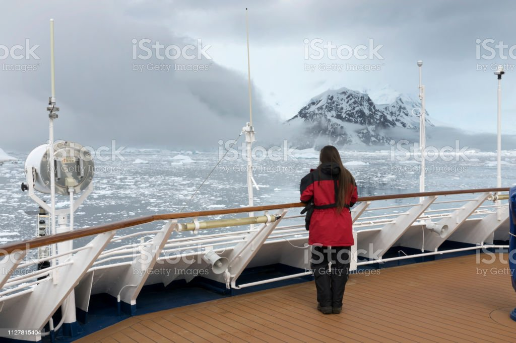 Woman ship view Antarctic Peninsula ice filled Neko Harbor mountain glacier Antarctica stock photo