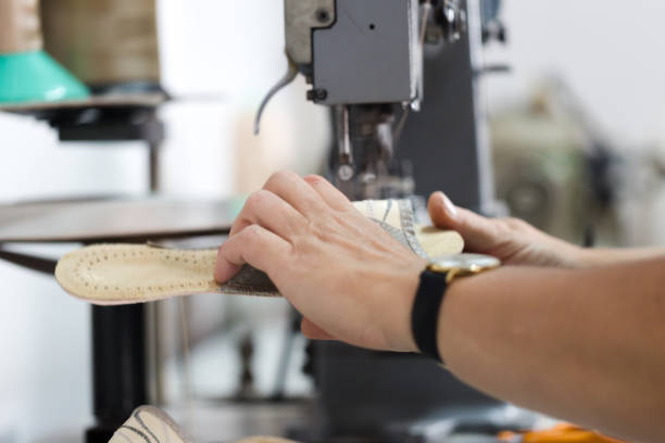 Woman shoemaker sewing flip flops on dedicated machine stock photo