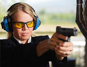 A woman in business clothing standing at the shooting range holding a handgun.