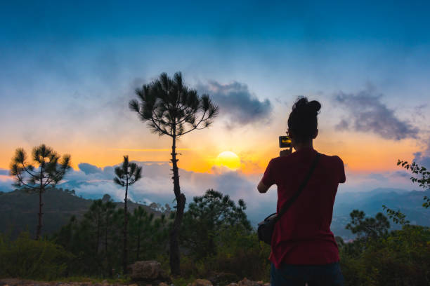 Woman shoots cloudy sunset view in the mountains through a smartphone. stock photo